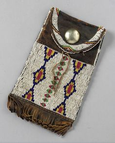 A CHEYENNE BEADED AND FRINGED HIDE DISPATCH CASE    composed of commercially tanned hide, glass beads, cotton thread, sinew and a German silver button.  Length 11 1/4 in.