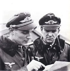 Luftwaffe aces Eric Hartmann and Gerhard Barkhorn going over a map on the Eastern Front. By this point, Hartmann had earned 352 victories and Barkhorn had Pin by Paolo Marzioli Luftwaffe, German Soldiers Ww2, German Army, Air Force Two, Erich Hartmann, Germany Ww2, Flying Ace, Battle Of Britain, Fighter Pilot