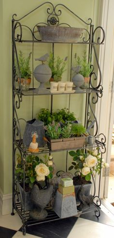 always like a wrought-iron bakers stand. I use this to house all my gardening bibs and bobs, little herb pots and my collection of grey tin pots, urns and birds. It makes a great display for the door out to the garden.