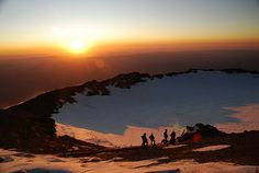 Mt Rainier summit crater at sunrise. Mount Rainier is a massive stratovolcano 54 miles (87 km) SE of Seattle in Washington, US. It is the most topographically prominent mountain in the contiguous US and the Cascade Volcanic Arc, with a summit of 14,411 ft (4,392 m). Mt. Rainier is one of the most dangerous volcanoes in the world, and it is on the Decade Volcano list. - and I live 30 miles away.