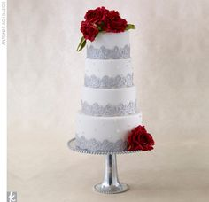 4 tier round cake with silver fondant embellishment and sugar-made red roses