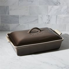 Revered by both professional chefs and home cooks since its 1925 debut, Le Creuset's classic French cookware is prized for its utilitarian good looks and unsurpassed heat retention. As beautiful as it is functional, this line of stoneware bakeware features superior performance in the oven or microwave and is ideal for baked goods and roasted dishes. Enamel-glazed in a truffle-tinted neutral that's exclusive to us, this covered baking dish is crafted of dense stoneware.
