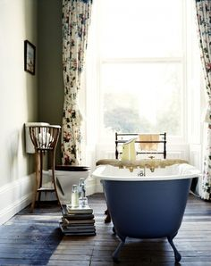 Rustic bathroom with floral curtains and blue tub