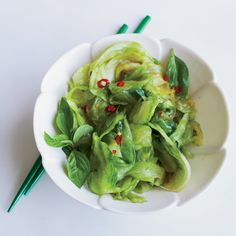 Quick and simple, this delicious Chinese dish features iceberg lettuce stir-fried with anchovies, thinly sliced Thai bird chile, fresh lemon and Thai basil.