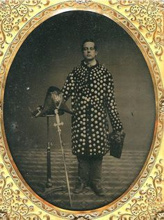 ca. 1860's, [hand tinted ambrotype portrait of gentlemen, possibly a part of the Knights Templar fraternal order, wearing an unusual disc-covered jacket, and holding a sword, mask, and hat]
