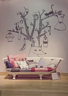I don't know which one I like more. The upcycled bath tub into a comfy couch. The colourful cushions. Or that artistic tree artwork wall decal.