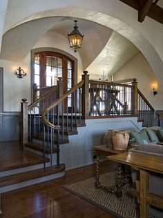 Love this double staircase entry::Makes the perfect place to put a large Christmas tree!  Old-world Lake House in South Carolina. Wright Design.