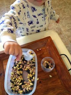 Invitation to play with a scooper and beans. Great way to practice early spoon skills!