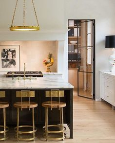 A sleek kitchen with a minimalist light fixture and gold and leather counter stools. A Modern Treatment of Traditional Form: natural white-oak floors with a flat, dry-looking finish and over-sized glass panes in the windows and doors providing an abundance of light. The Banks Development Co.