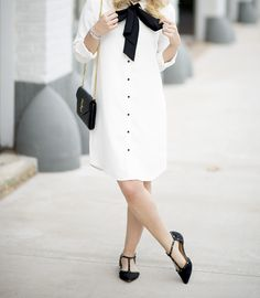 white shirt dress with black bow, studded flats