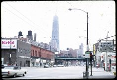 West Chicago Avenue and John Hancock Center under construction (1968), by William C. Brubaker. At the intersection of Chicago Avenue and New Orleans Street.