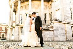 Dramatic city wedding image of bride and groom kissing in front of building with columns and cobblestone. Image by Philadelphia wedding photographer Ben Weldon of Weldon Weddings.