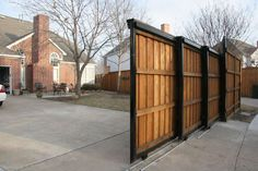 We envisioned a metal framed wood sliding gate.  We like the option of several panels seen here given the larger span of the driveway opening.
