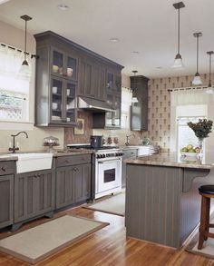 The cool undertone to the grey adds a very serene look to the kitchen, as well as the patterned wallpaper with the pop of a contrasting cool red hue
