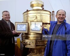 The manufacturers of the largest operating Russian samovar in the world show diplomas of the Records of Ukraine Book during the presentation of their product at the international exhibition MARGO-2004 in Kiev 02 March 2004. The handmade samovar, which is 1,75 meters high, wheighs 250 kilos, can produce 295 liters of tea. AFP PHOTO/ Sergei SUPINSKY