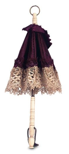 """French Bone-Handled Silk Parasol for Poupee    8"""" (20 cm.) having carved bone handle and brass framework that allows the parasol to open and close,the parasol is fitted with original burgundy silk and a wide band of finely woven cotton lace. Excellent condition. French,circa 1875."""