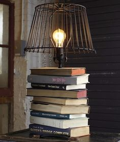 Drill a hole through each volume in the stack, string some lamp wire through, then glue a socket to the top book