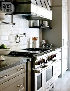 Shelf + subway tile + aged pewter detailing on range hood in kitchen by Nam Dang Mitchell