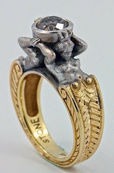Two Tone Gold Sculpted Man and Woman holding jewel by SERGEY ZHIBOEDOV