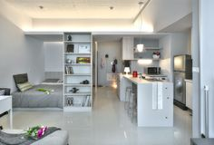 A clean and organized tiny apartment has storage shelves and cabinets and is decorated in mostly white.