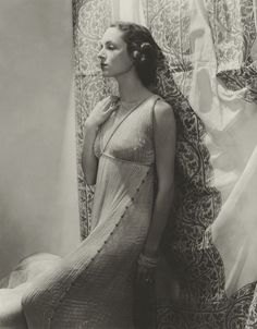 1935, Mrs. William Wetmore modelling a Delphos gown in front of Fortuny fabric. Originally published in Vogue.