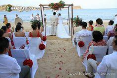 Ceremonia con detalles florales en rojo ideal para tu boda en playa por Bodas Huatulco