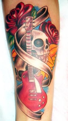 A vibrant and colorful guitar tattoo with skulls and flowers.  The guitar is drawn with a ribbon surrounding it. The skulls and the flowers are seen behind the guitar in full vibrant colors.