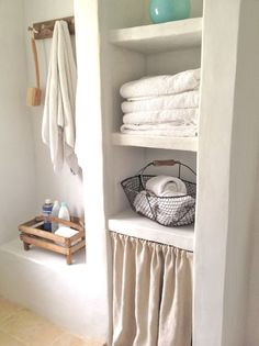 Peninsula Bathroom. Skirted storage with open plaster shelves... vintage robe hooks.