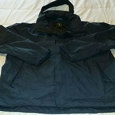 MEN'S lined raincoat. Size XXL. Like new! Incredible men's raincoat. Lined for warmth.  Hood can be rolled up and stored at back of neck. Color is navy blue. Lots of pockets. Three on front of jacket. One of those is a hidden Napoleon pocket near zipper  (shown in photos). Two more large pockets inside, one is shown in photos. Like new condition. Chest measures 26 inches across laying flat. 30 inches long from the shoulder. Fabric content shown in the photos. Aigle Jackets & Coats