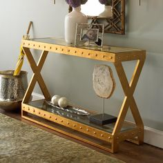 Glass Top Studded Console with clean lines and a bottom shelf for added storage, function meets fashion. Available in Gold Leaf or Satin Nickel