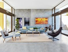 The concrete encased living room in this coastal family home in Perth, is softened with shades of blue, and yellow. Photography: Jack Lovel | Stylist: Anna Flanders | Story: Australian House & Garden