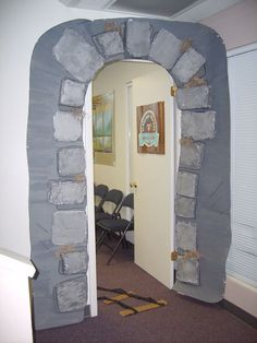 """Doorway idea:  Plastic tablecloths and bits of torn and painted cardboard for """"stone bricks?"""""""