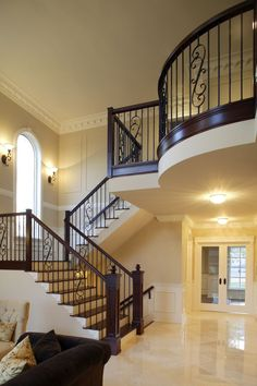 Amazing Stair Designs -                                                              The large landing at the top of the stairs pushes out over the marble floor of the entryway in a style that is reminiscent of a balcony.