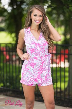 This sleeveless romper is perfect for all of your summer adventures! It featuresa wrap style front with overlapping fabric creating a v-neckline. The bold, leafy pattern features aqua, white, and hot pink - a trendy color combination this summer! There's also a cute collar and a fabric tie at the waist, plus the fabric is so soft and comfortable!