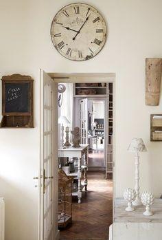 Une entrée lumineuse, blanche et crème, aux détails charmants : horloge aux tons vieillis, petit tableau et luminaires stylisés aux accents campagnards.