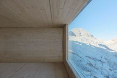 Inside, this timber-lined cabin features three resting platforms that face towards the valley through a large panoramic window. Its only decoration is a hunting trophy of a pair of deer antlers.