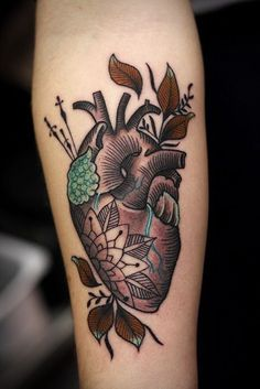 Tattoo on the forearm of the girl - heart with leaves