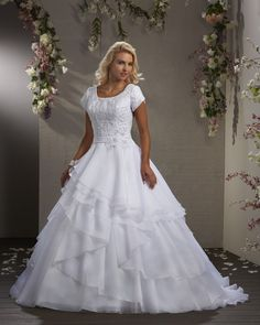 An intricate floral lace covers this demure bodice with tulip sleeves. A band wraps around the waist with lace and organza petal motif. Asymmetrical layers flow softly down the full A-line skirt and train. | Bonny Bliss Bridal: Style 2410 | Modest Wedding Gown