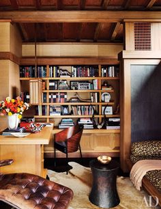 A home office featuring redwood shelves and desk which are original to the house | archdigest.com