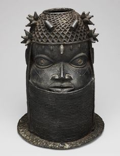 Edo, Court of Benin, Nigeria.       Altar Head for an Oba (Uhunmwun Elao), 18th/early 19th century. This commanding brass head served as the elaborate pedestal for a sculpted elephant tusk. It was commissioned by a newly enthroned oba to stand on an altar commemorating a previous oba, probably his father