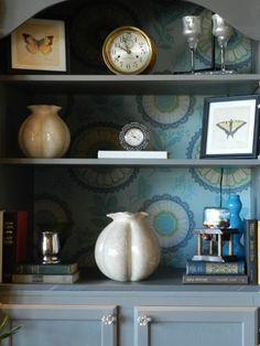 Wallpaper backed bookshelves with doors added.