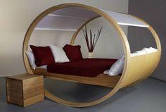 Com a sensação de que está balançando, essa cama apresenta um formato inovador, como se fosse um balanço. Ela apresenta vários contrastes, combinando um ar rústico com um design inovador. Feita de madeira, a forma é elíptica, com estrutura vazada e uma cobertura branca.