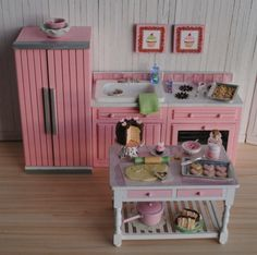 Miniature Pink Kitchen Appliances, A Baking Table With Sugar Cookies In the Making, And A Pair Of Cupcake Wall Hangings