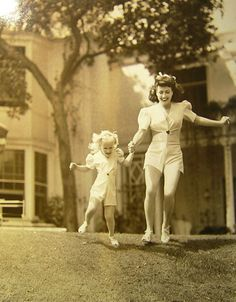 Joan Crawford and her adopted daughter, Christina, wearing matching outfits in 1943-- mommy dearest...