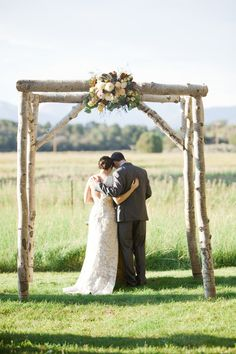 love the log arbor with the flowers, rustic  and elegant.  Perfect for the mountain wedding!