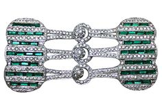 As described by Little Treasures 1920s large pot metal belt buckle in an unusual size and design, set with green faceted baguettes and clear round rhinestones.