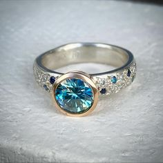 A 1 carat 6.5mm round pale green/blue moissonite set in rose gold on a 4mm wide band in white gold ,diamonds and sapphires.