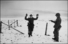 An American soldier capturing a German soldier. Battle of the Bulge:   December 23rd-26th, 1944. (Robert Capa)