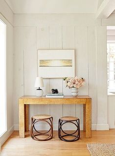 Midcentury-inspired, feminine styled console vignette with mis-matched stools, a…
