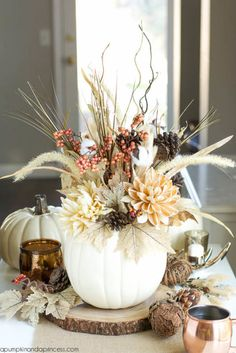 A white faux pumpkin adds fall flair to this centerpiece. The arrangement of pinecones, branches and burlap leaves is both rustic and elegant.